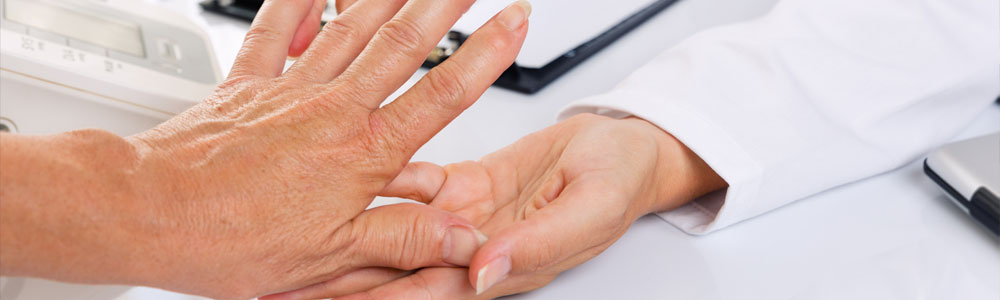 Hand being examined by a medical professional