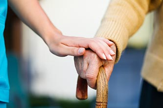 A nurse's hand supporting an elderly person with a walking stick