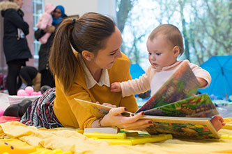 Nursery worker reading with baby